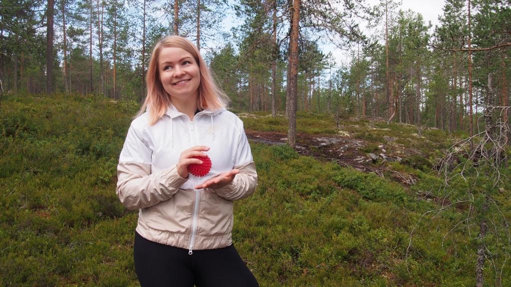 Jenna Möttönen kuvattavana havupuumetsässä. Kädessään hän pitelee punaista nystyräpalloa, jota voi käyttää lihastenhuoltoon.