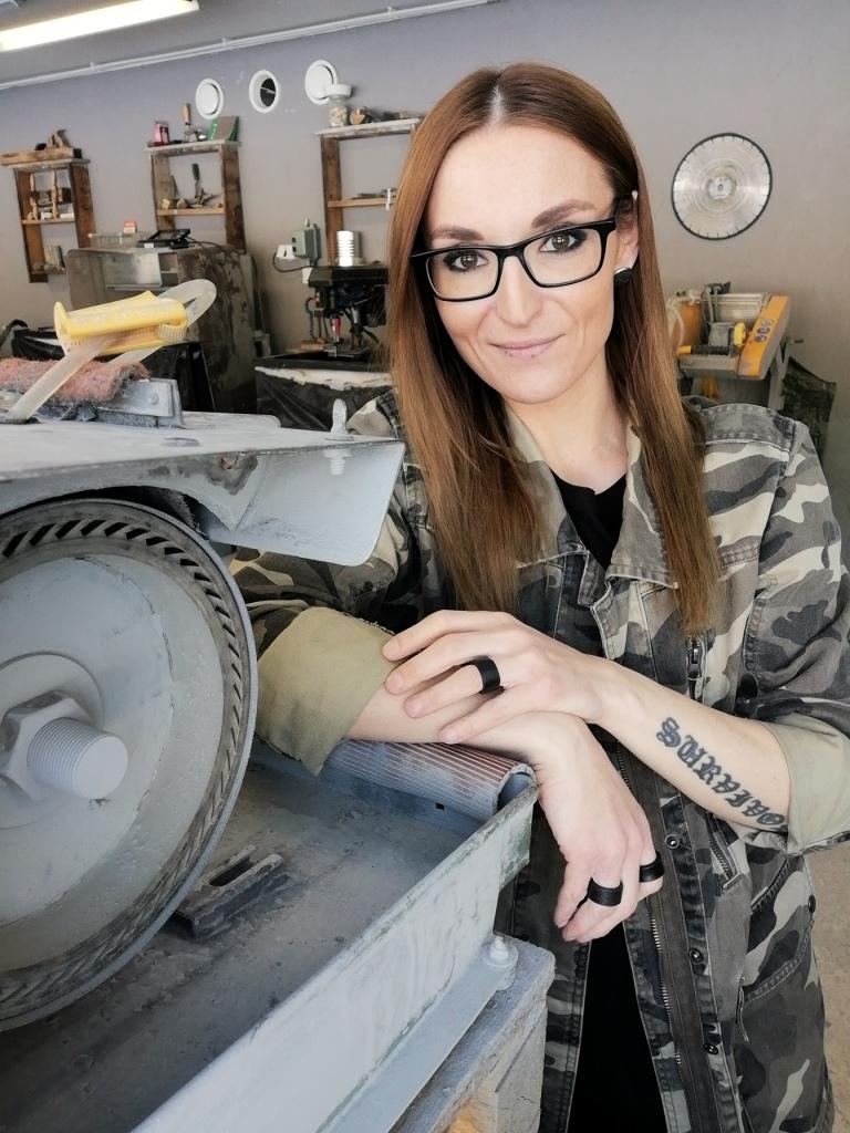 Sara Vaskivuo nojaa kivien käsittelyssä tarvittavaan laitteeseen ja hymyilee kameralle.