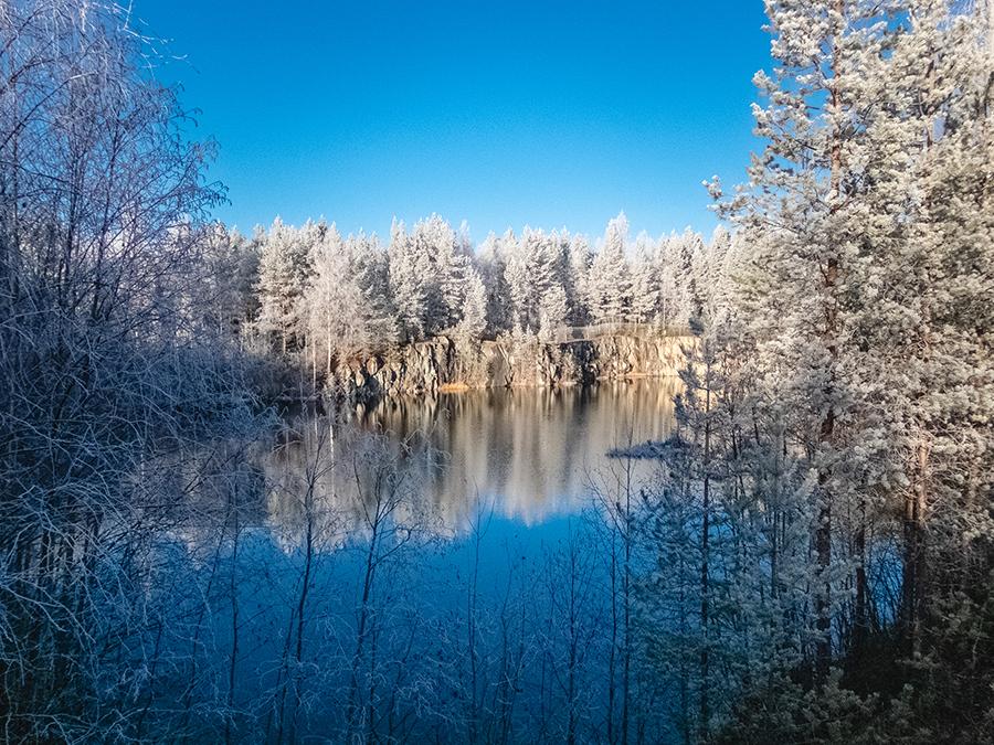 Vedellä täyttynyt vanha avolouhos. Louhoksen ympärillä puita talvisessa huurteessa.