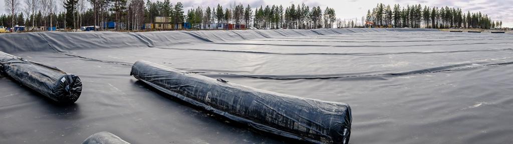 Sotkamon Silverin hopeakaivoksen rakennusvaiheen kuva, jossa asennetaan kalvorakenteita altaan pohjalle.
