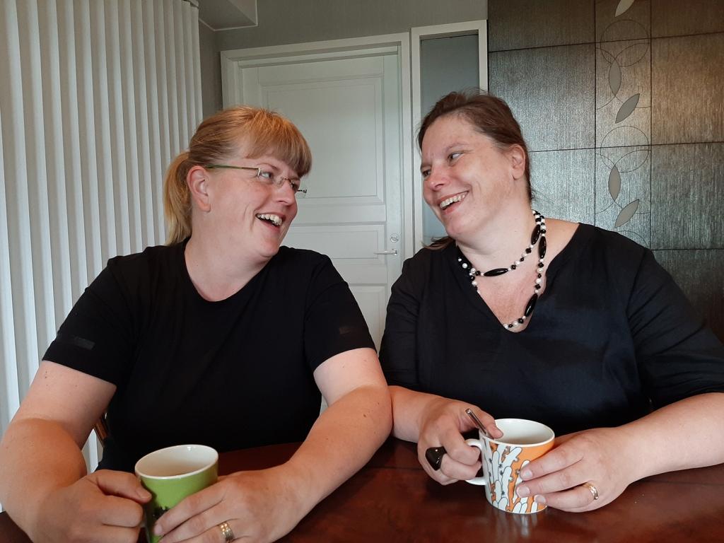 Nauravat naiset katsahtavat toisiaan. Molemmilla kahvimukit kädessä ja he istuvat pöydän ääressä.