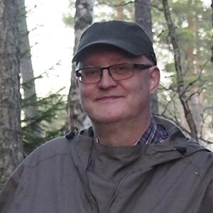 Reima Leinonen metsässä ja nojaa puun kylkeen.