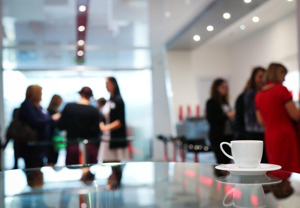 Naisia ryhmissä kahvitauolla keskustelemassa keskenään.