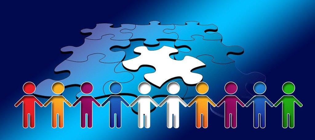 Piirroskuva palapelistä ja edustalla olevista eri värisistä ihmishahmoista, jotka pitävät toisiaan kädestä kiinni. Kuvaa yhteistyötä.
