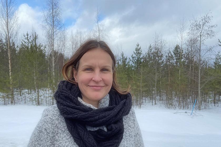Hymyilevä Tiina Veijola kuvattuna ulkona talvisessa maisemassa.