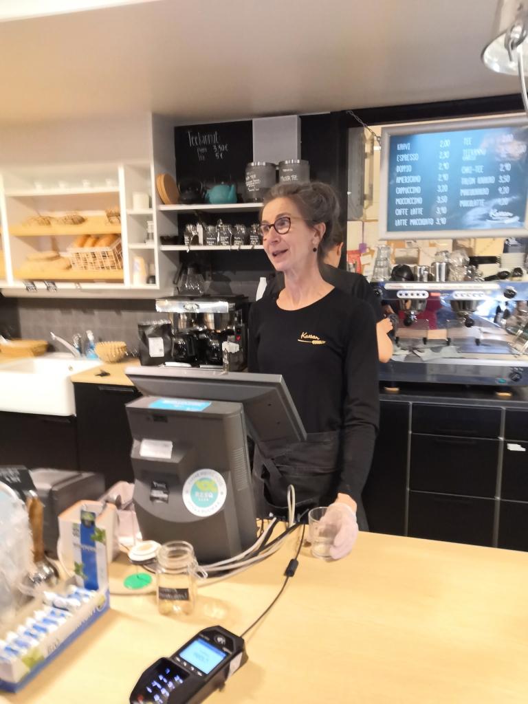 Kahvilassa nainen seisoo kassakoneen takana. Taustalla näkyy myytäviä leipomotuotteita.