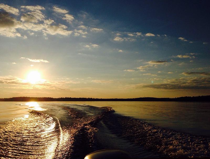 Perämoottorin ja veneen perälaineet näkyvät järven pinnalla.