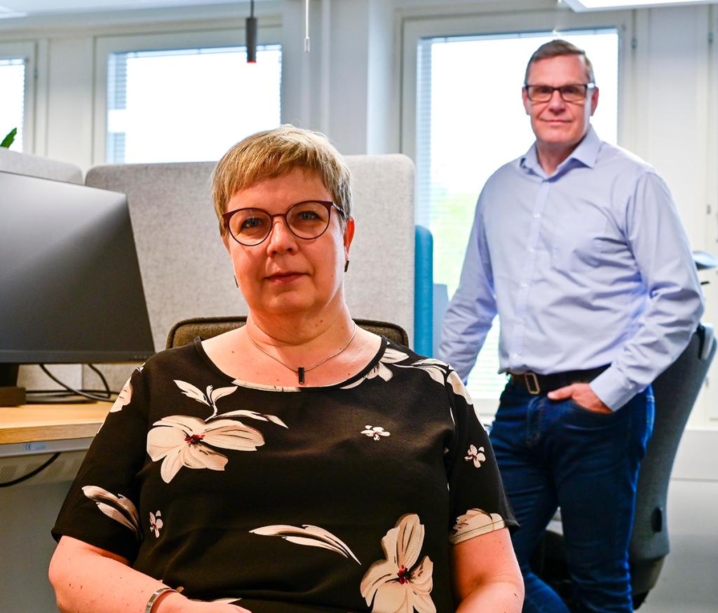 Nainen istuu ja mies seisoo toimistossa