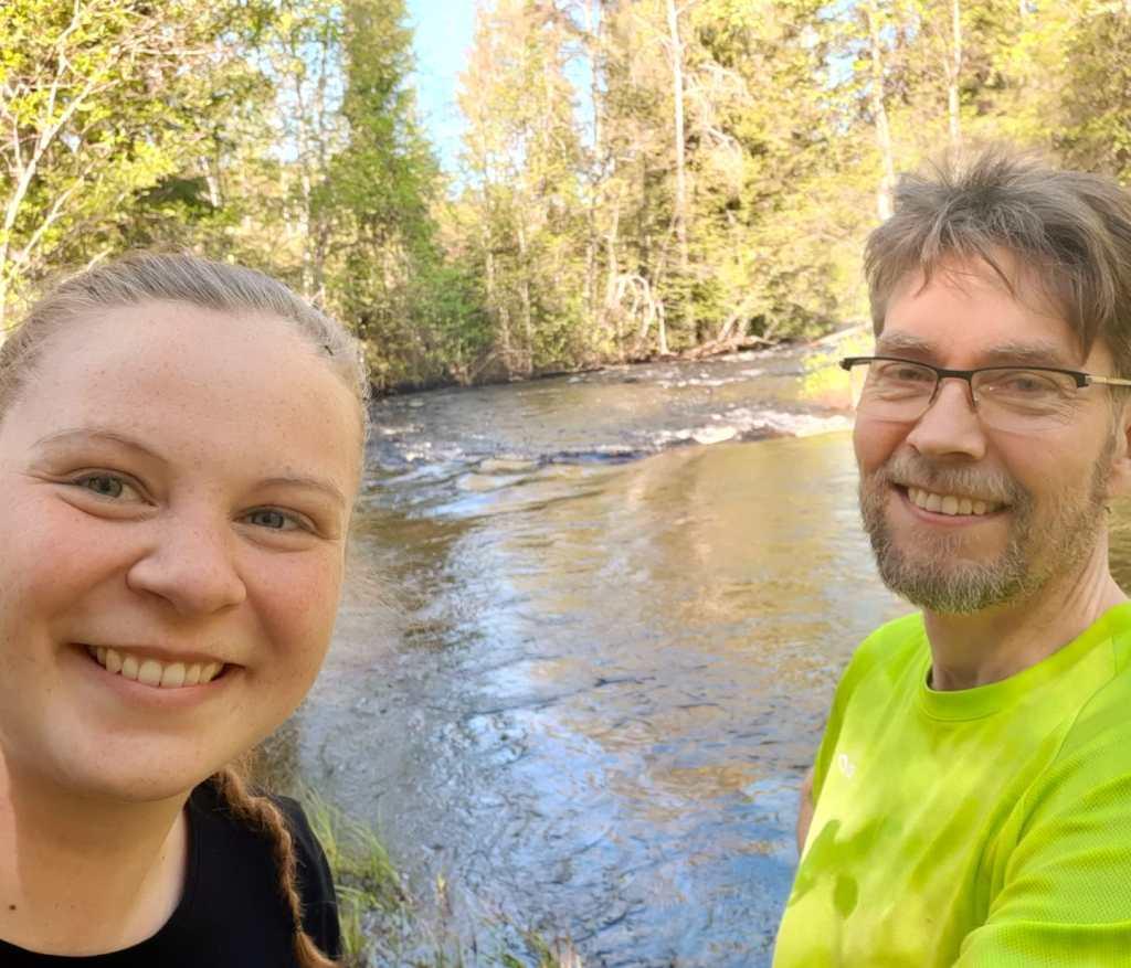 Nainen ja mies alkukesällä joen rannalla. Katsovat kameraan ja hymyilevät.