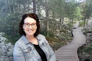 Nainen istuu takanaan maisema, jossa puinen kävelypolku johtaa horisonttiin.