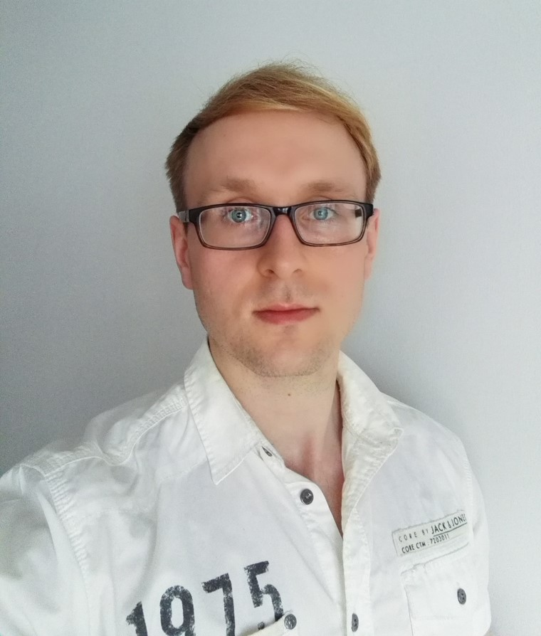 Valokuva silmälasipäisestä miehestä kauluspaita päällä.