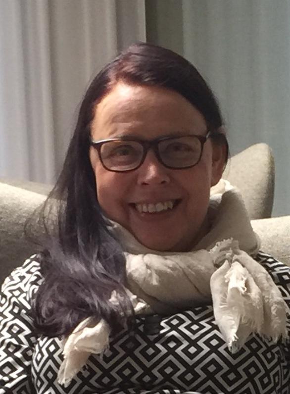 Hymyilevä tukkatukkainen nainen silmälasit päällä istuu tuolissa.