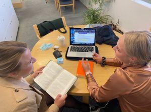 Kaksi naista keskustelee opintosisällöistä. Toisella on auki kirja, toisella kannettava tietokone.