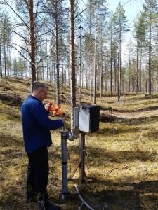 Pystykokoinen valokuva. Mies nostaa tikkua maahanpystytystä putkesta. Ympärisllä on metsämaisema.