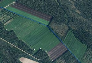 Satelliittikuva peltomaisemasta. Keskellä kuvaa kulkee sinisellä merkitty valtaoja.