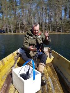 Vene järvellä, jossa styroksinen astia ja miehen pitelemä mittari.