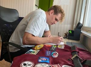 Mies kirjoittaa muistiinpanoja työpöydän äärellä. Pöydällä on myös violetti opiskelijahaalari, jonka lahkeissa on useita tarroja.