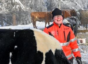 Nainen hymyilee ulkoilevien lehmien keskellä työhaalareissa.