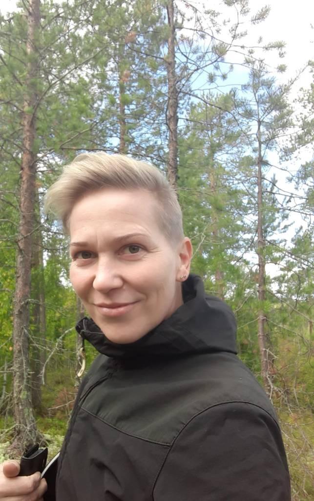 Nainen katsoo kameraan. Takana on metsämaisema.